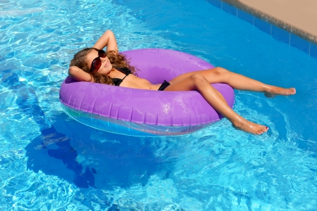 bikini children girl with sunglasses relaxed on purple inflatable pool ring Stock Photo