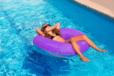 bikini children girl with sunglasses relaxed on purple inflatable pool ring photo