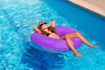 schwimmring: bikini Kinder Mädchen mit Sonnenbrille auf lila aufblasbaren Pool Ring entspannt
