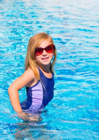 blond kid girl in blue pool posing with sunglasses smiling photo