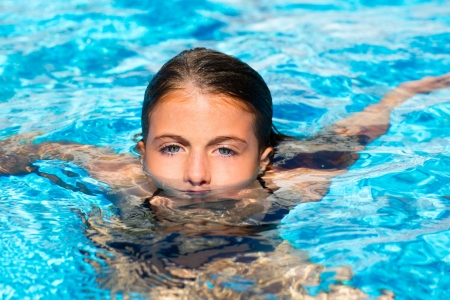 swimming pool float: beautiful blue eyes kid girl at the pool with face in water surface