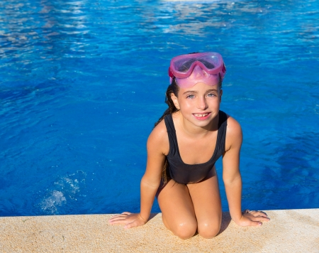 Blue eyes kid girl on knees on blue pool poolside with snorkel pink glasses photo