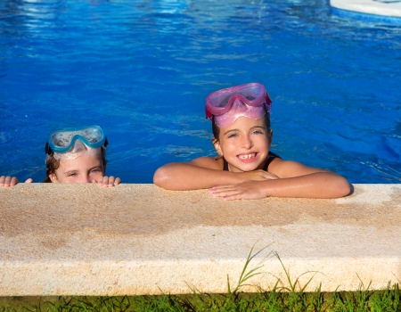 Blue eyes children girls on on blue pool poolside smiling with snorkel glasses Stock Photo - 15907739