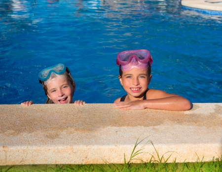 Blue eyes children girls on on blue pool poolside smiling with snorkel glasses photo