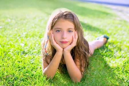 blue eyes children girl relaxed on the garden grass lying with hands in face photo