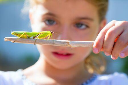 wetenschappelijke naturalist bioloog kid meisje op zoek bidsprinkhaneninsect closeup