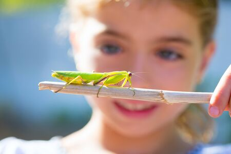 scientific naturalist biologist kid girl looking praying mantis insect closeup Stock Photo - 15907768