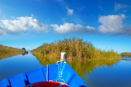 Blue boat sailing in Albufera lake of Valencia in a sunny blue sky day photo