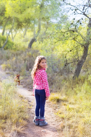 children girl walking in the pine forest with doggy around photo