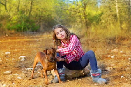 children girl sitting in the pine forest holding little dog mini pinscher photo