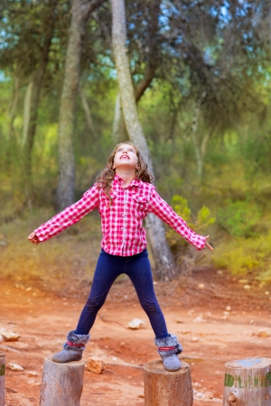 kid girl climbing tree trunks with open arms having fun in the pine forest photo