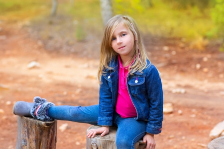 children girl relaxed on a tree trunk in the forest outdoor photo