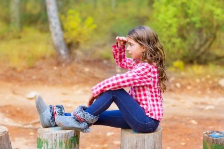 lejos: Kid niña sentada en el tronco del bosque mirando a lo lejos con la mano en la frente Foto de archivo