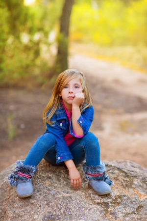 bored face: blond kid girl pensive bored expression in the forest outdoor sitting on a rock