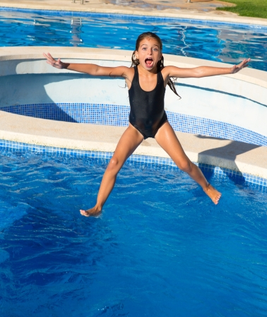 plunge: children girl jumping to the blue pool with black swimsuit in summer vacations Stock Photo