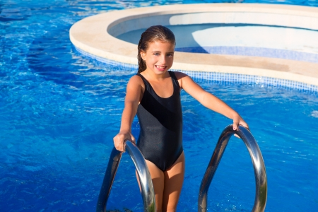 children girl on the blue pool stairs with black swimsuit in summer vacations photo