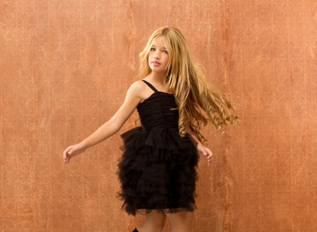 black dress kid girl dancing and twisting on vintage background photo