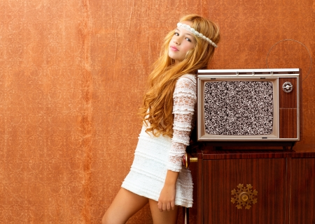 Blond vintage 70s kid girl with retro wood tv on wallpaper photo