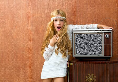 Blond vintage 70s kid girl with retro wood tv surprised expression gesture photo