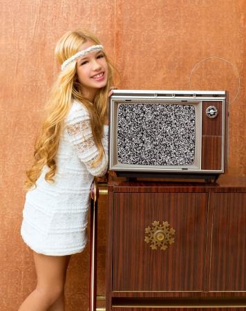 Blond vintage 70s kid girl with retro love old tv on wallpaper photo
