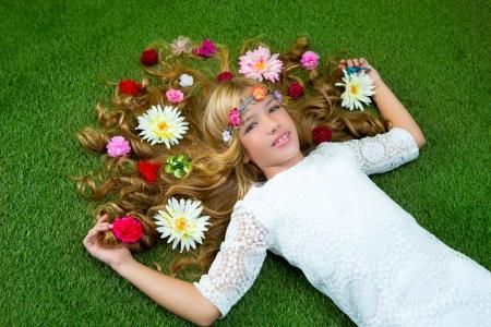 lying on grass: Blond spring children girl with flowers on hair over green grass floor