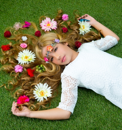 Blond spring children girl with flowers on hair over green grass floor photo
