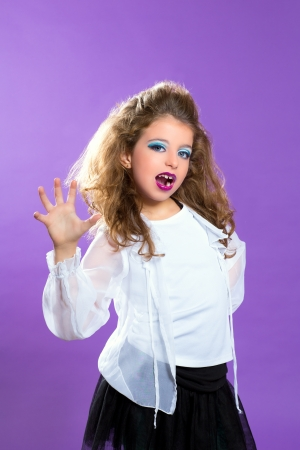 Children fashion makeup kid girl trying to scare gesture on purple photo
