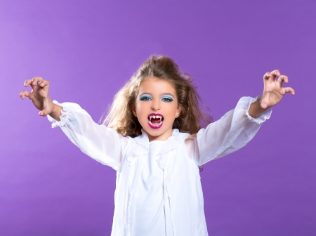Children vampire makeup kid girl on purple background photo
