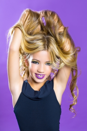 Blond children fashiondoll girl fashion makeup on purple background photo