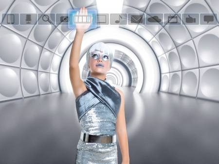 holographic: futuristic kid girl in silver touching finger icons on glass transparent holographic screen Stock Photo