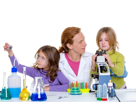 investigating: children girls and teacher woman at laboratory on school chemical class Stock Photo
