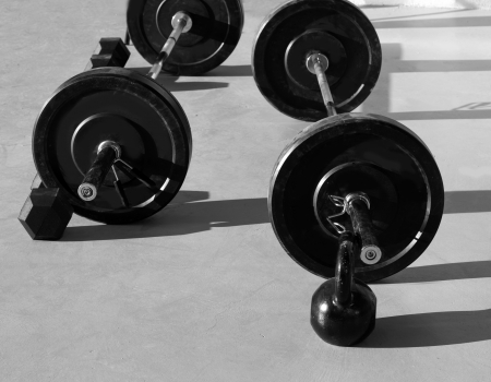 Kettlebells at crossfit gym with lifting bar weights fitness equipment