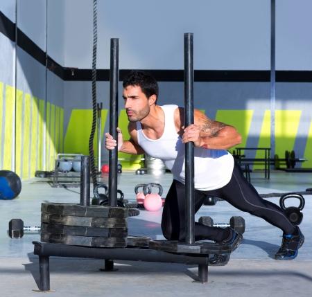 hombre empujando: Trineo Crossfit hombre pushing pesas ejercicio entrenamiento