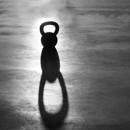 crossfit: Crossfit Kettlebell weight backlight and shadow on the gym floor Stock Photo