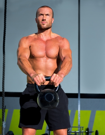 Crossfit Kettlebells swing exercise man workout at fitness gym Stock Photo