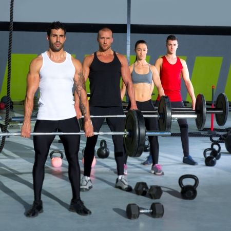 levantar pesas: gimnasio grupo con entrenamiento barra de levantamiento de pesas en el ejercicio crossfit Foto de archivo