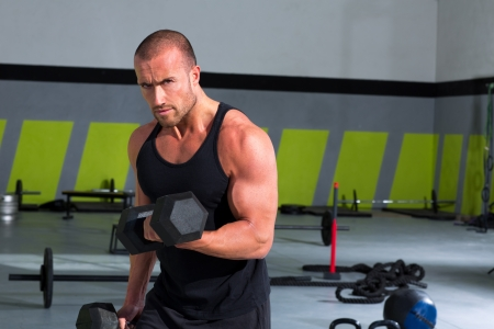 bodybuilder training: Gym man with dumbbells weights lifting exercise crossfit fitness workout Stock Photo