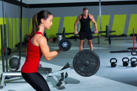 girl dumbbell and man weight lifting bar workout  at crossfit gym Stock Photo