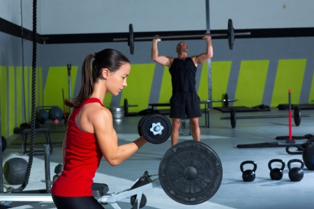 girl dumbbell and man weight lifting bar workout  at crossfit gym photo