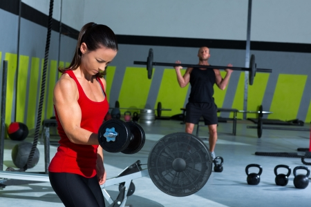athletic body: girl dumbbell and man weight lifting bar workout  at crossfit gym Stock Photo