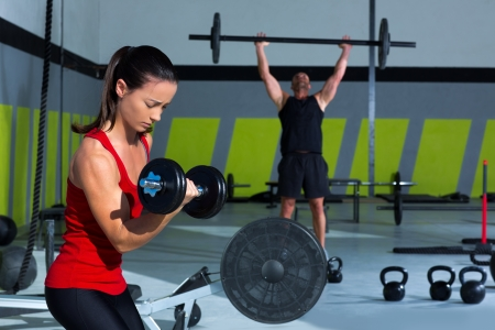 girl dumbbell and man weight lifting bar workout  at crossfit gym Stock Photo - 17050633
