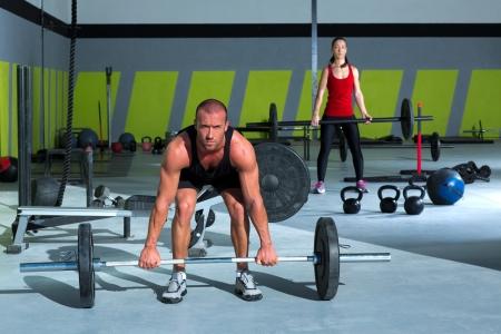 halterofilia: gym hombre y la mujer con bar entrenamiento de levantamiento de pesas en el ejercicio crossfit