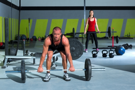 weightlifting equipment: gym man and woman with weight lifting bar workout in crossfit exercise Stock Photo