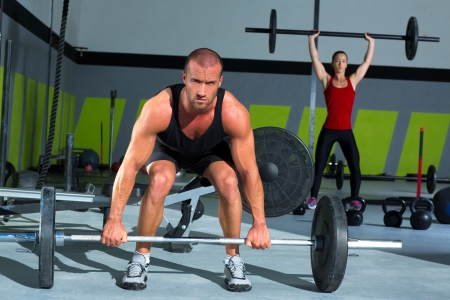 heavy lifting: gym man and woman with weight lifting bar workout in crossfit exercise Stock Photo