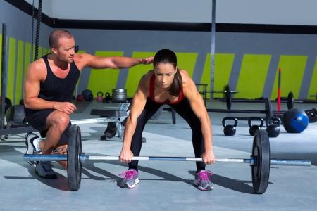 levantamiento de pesas: gym hombre entrenador personal con entrenamiento de levantamiento de pesas mujer bar en el ejercicio crossfit Foto de archivo