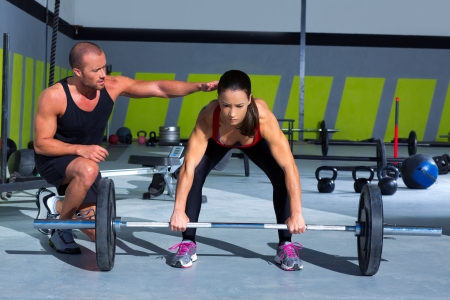 personal trainer: gym personal trainer man with weight lifting bar woman workout in crossfit exercise Stock Photo