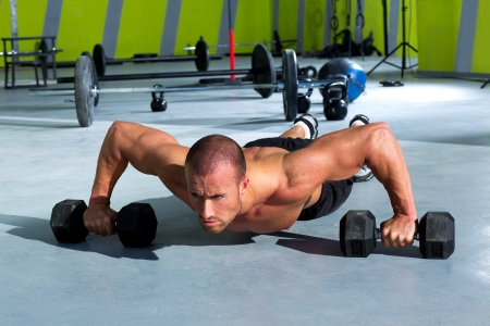 pushup: Gym man push-up strength pushup exercise with dumbbell in a crossfit workout Stock Photo