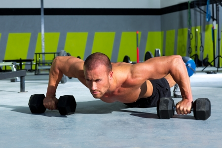 push: Gym man push-up strength pushup exercise with dumbbell in a crossfit workout Stock Photo