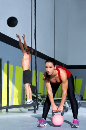 weightlifting: Crossfit gym Kettlebell woman and jumping wall ball man  workout at gym Stock Photo