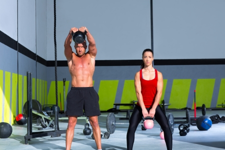 Kettlebells swing crossfit exercise man and woman workout at gym